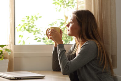 Woman holding coffee cup thinking about symptoms of PCOS | Dallas IVF | Frisco & Dallas, TX
